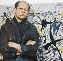 Jackson Pollock standing before one of his paintings